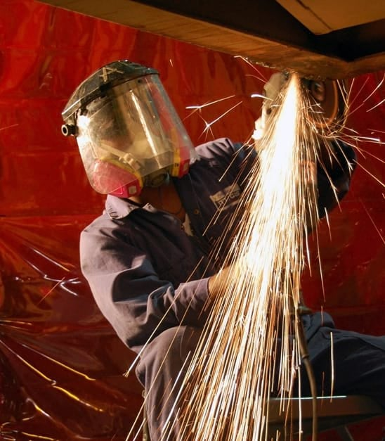 Auto body service expert performing metal work on car with face shield on